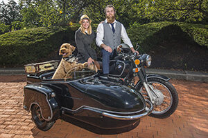 Couple on a BMW motorcycle with dog in sidecar